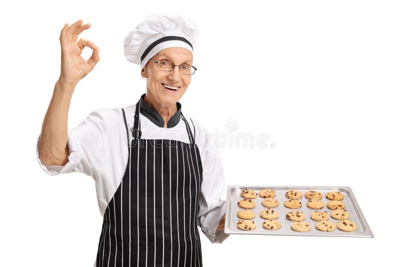 Älterer Bäcker, der Behälter mit Plätzchen hält und okayzeichen macht lizenzfreies stockbild
