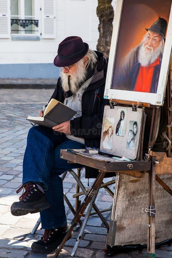 Älterer bärtiger Künstler, der berühmten bei Place du Tertre im Montmartre arbeitet stockbild