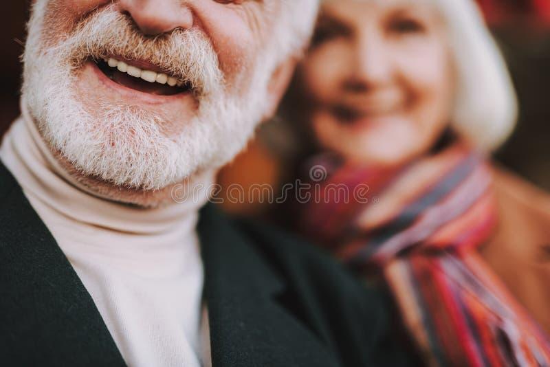 Älterer bärtiger Mann im schwarzen Mantel, der positive Gefühle ausdrückt stockfotografie