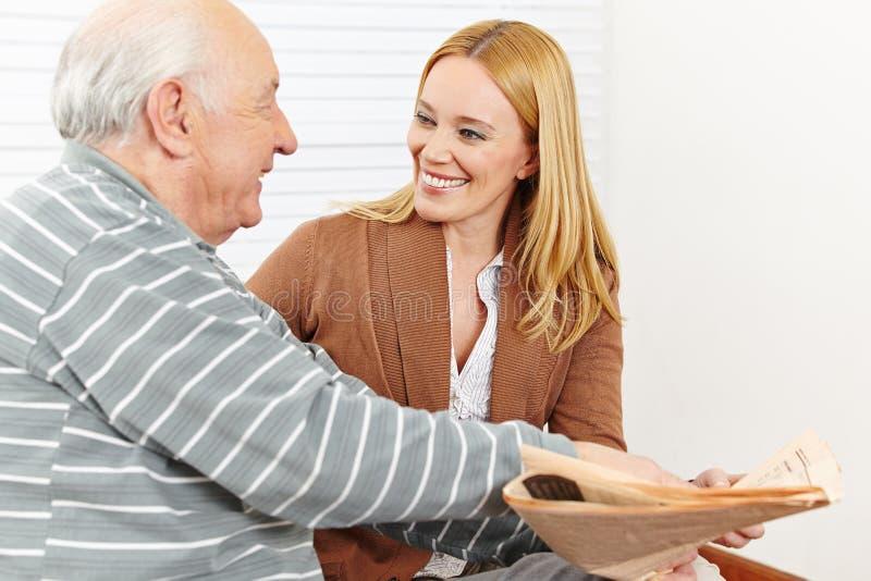 Älterer Bürger mit Frauenlesung lizenzfreie stockbilder