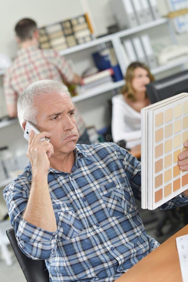 Älterer Büroangestellter schaut verwirrt stockfoto