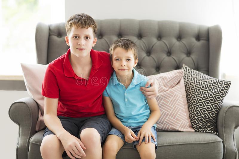 Älterer Bruder auf dem Sofa, das jüngeren Bruder umarmt stockfoto