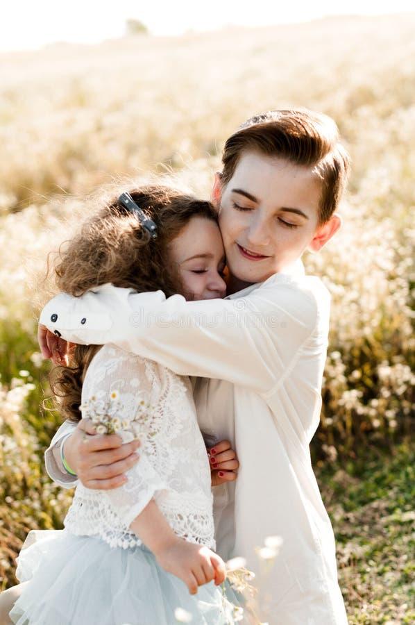 Älterer Bruder umarmt seine kleine Schwester stockbild