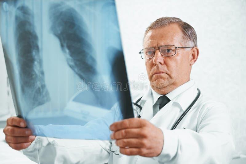 Älterer Doktor überprüft Röntgenstrahlbild von Lungen stockbilder