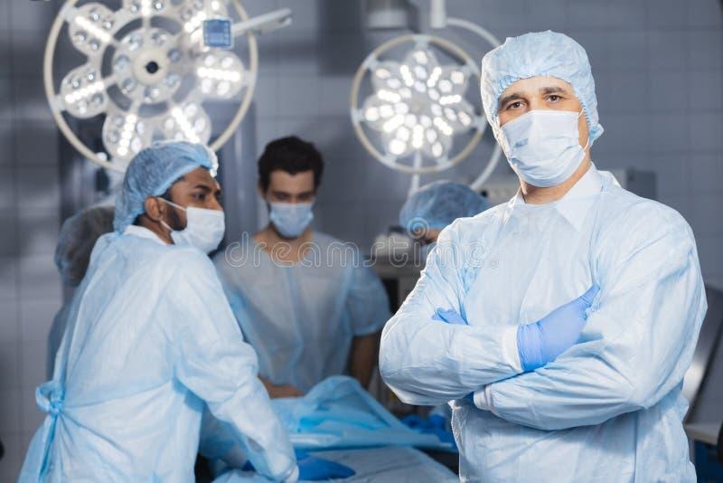 Älterer Doktor, Chirurg, der medizinische Schutzmaske im Operationsraum trägt stockfotos