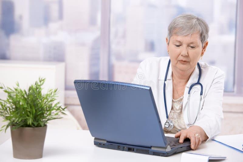 Älterer Doktor, der Bildschirm betrachtet lizenzfreies stockbild