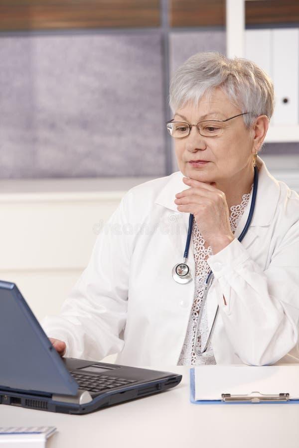 Älterer Doktor, der Computer betrachtet lizenzfreie stockfotografie