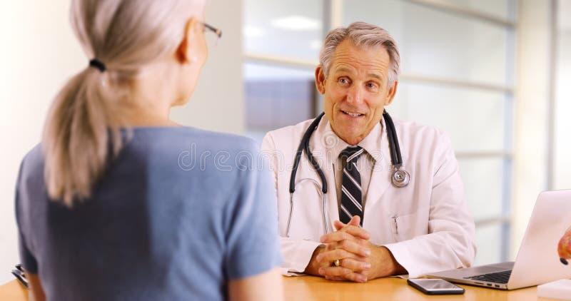 Älterer Doktor, der Gesundheitsinteressen mit älterer Frau bespricht lizenzfreies stockfoto