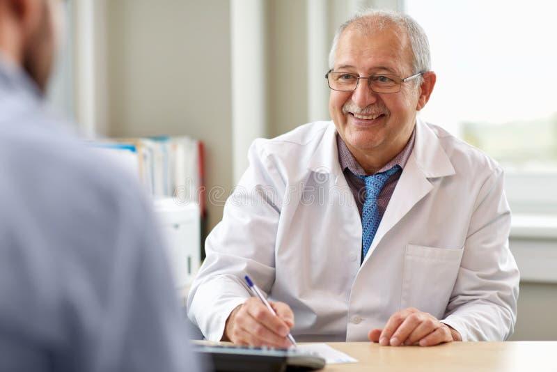 Älterer Doktor, der mit männlichem Patienten am Krankenhaus spricht lizenzfreie stockfotos