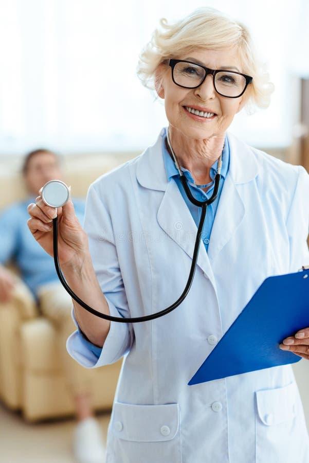 Älterer Doktor, der nett lächelt und Stethoskop hält lizenzfreie stockfotografie