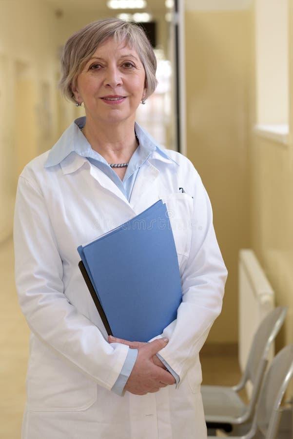 Älterer Doktor mit Patientenakten stockfoto