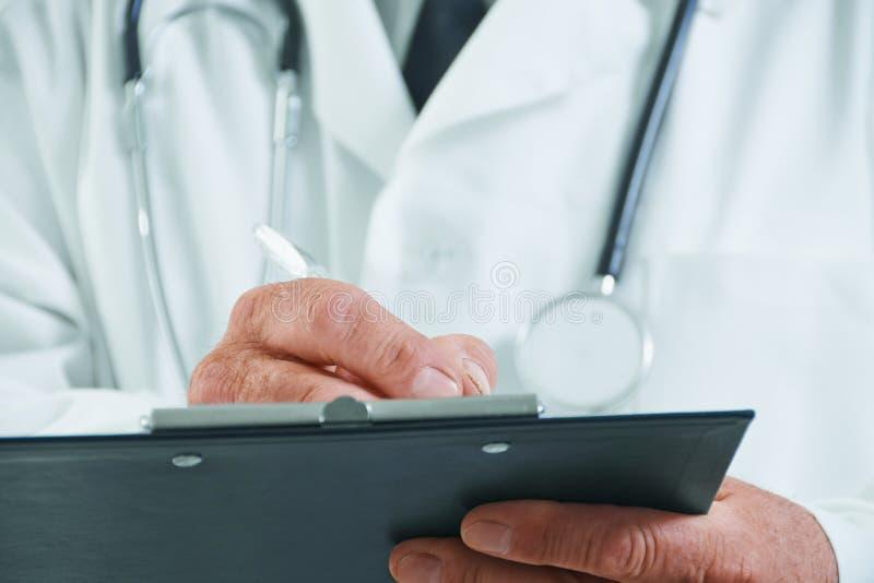 Älterer Doktor schreibt medizinische Anmerkungen stockfotos