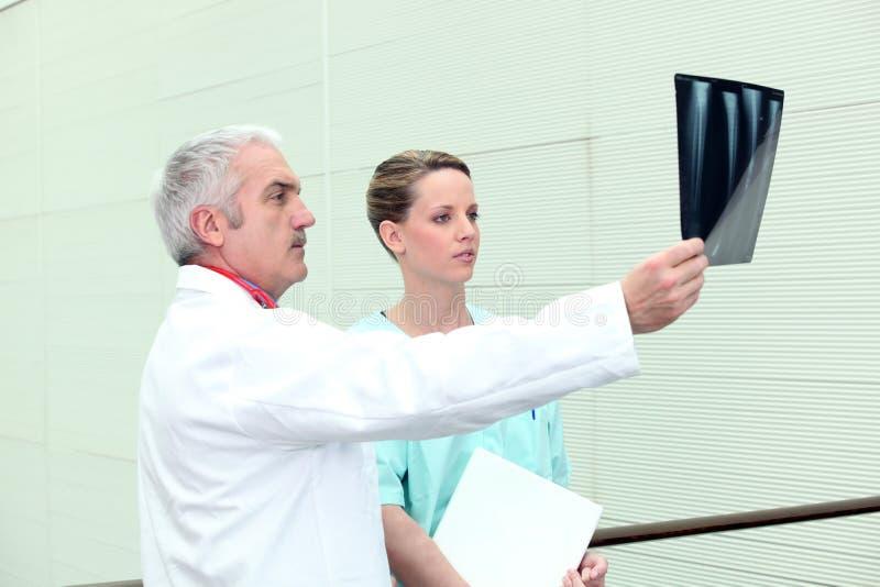 Älterer Doktor und Krankenschwester, die einen Röntgenstrahl überwacht lizenzfreie stockfotos