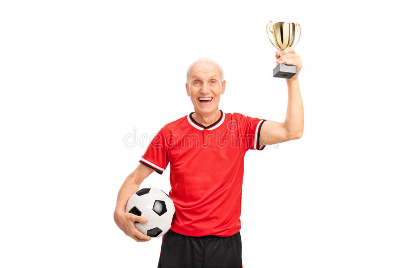 Älterer eine Trophäe haltener und feiernder Fußballspieler stockfotografie