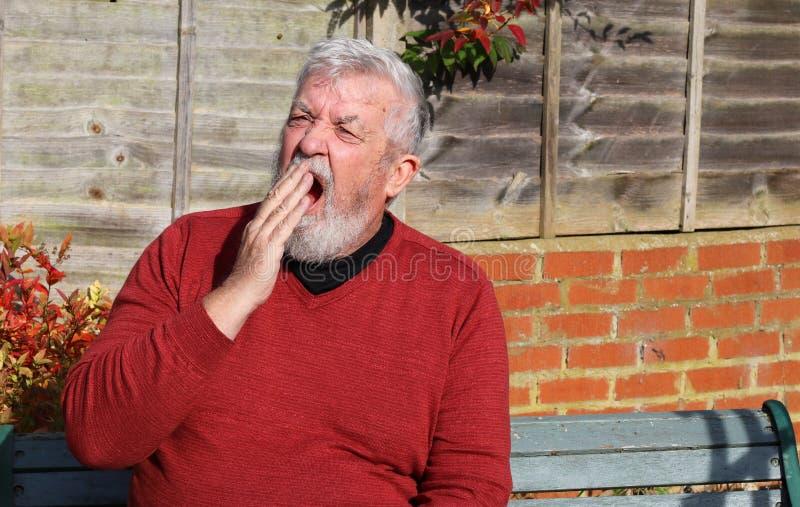 Älterer ermüdeter und gähnender Mann stockfoto