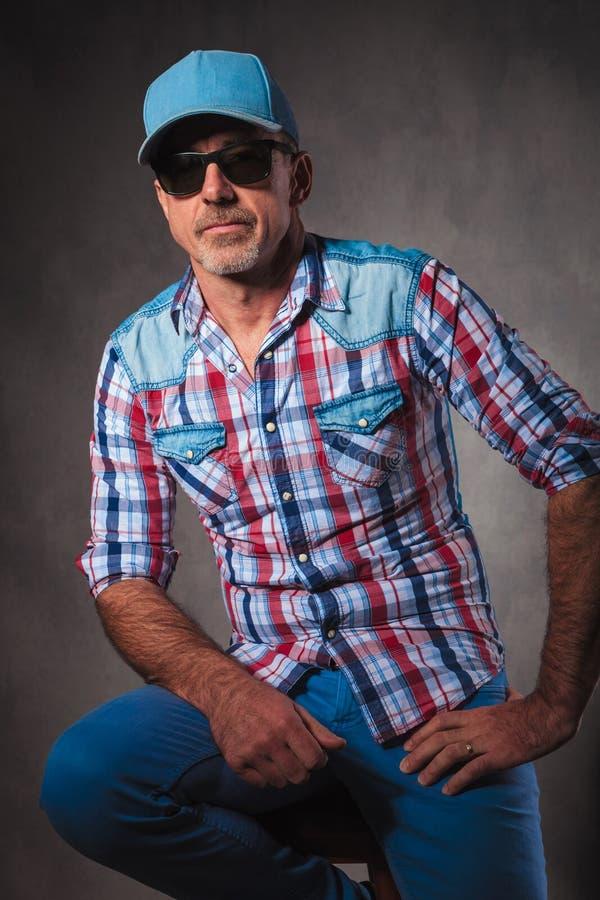 Älterer Fernlastfahrer, der auf einem Stuhl im Studio stillsteht stockfoto