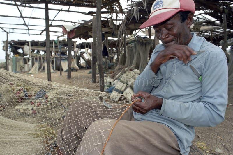 Älterer Fischer sitzt, um Fischnetz zu reparieren stockfotos