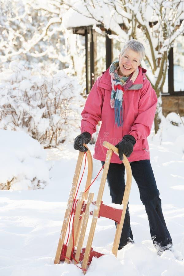 Älterer Frauen-Holding-Schlitten in der Snowy-Landschaft stockfoto