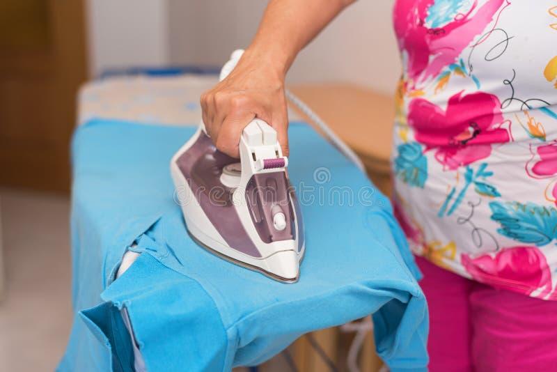 Älterer Frauenabschluß, der oben Kleidung bügelt lizenzfreie stockfotografie