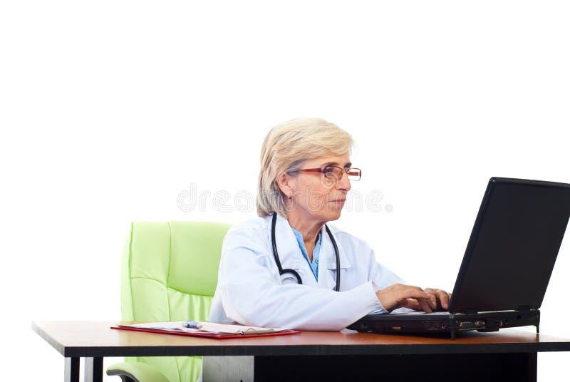 Älterer Frauendoktor, der auf Laptop schreibt stockfotografie