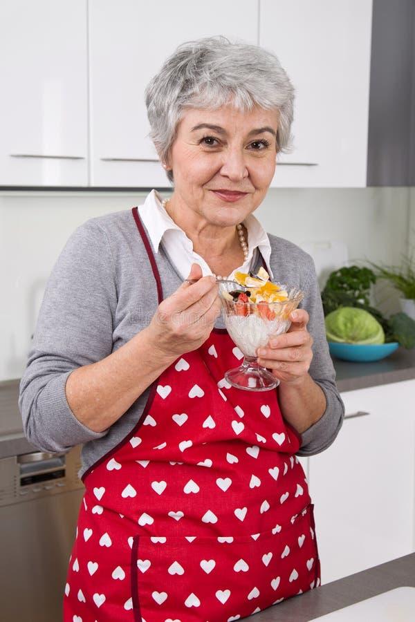 Älterer Frauenkoch und essen in der Küche lizenzfreie stockfotos