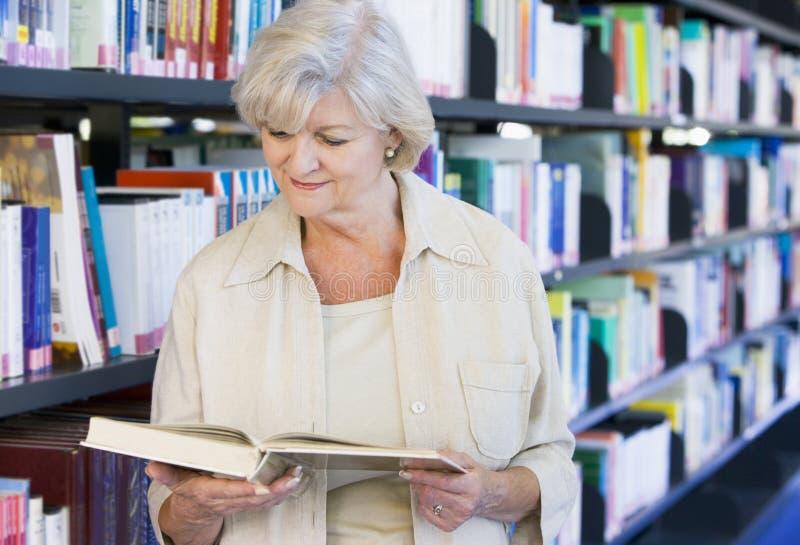 Älterer Frauenmesswert in einer Bibliothek lizenzfreie stockbilder