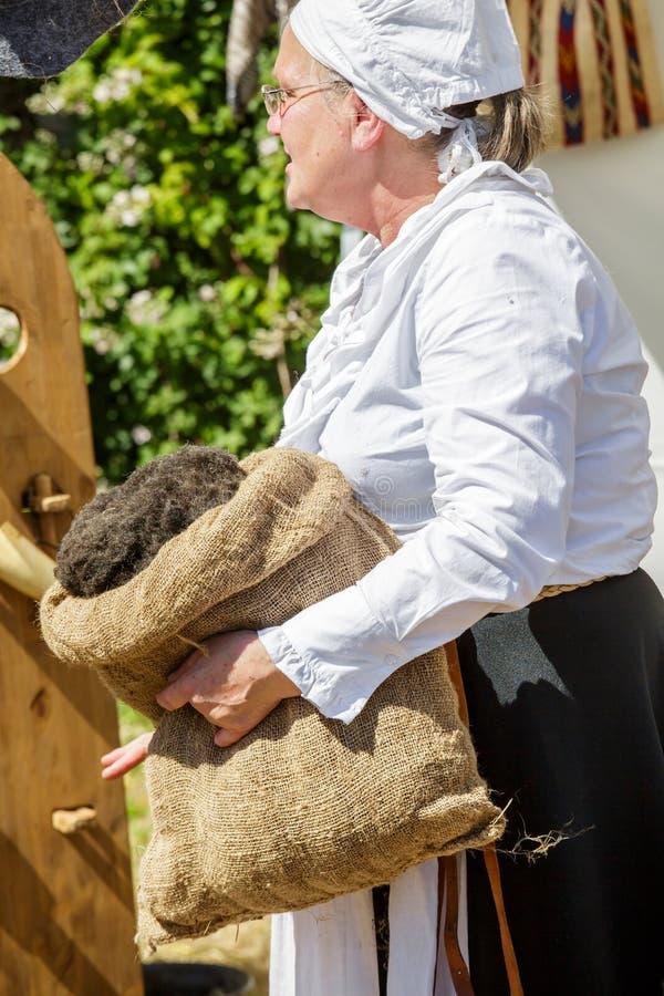 Älterer Frauenspinner, der Sack mit Baumwolle hält lizenzfreie stockfotos