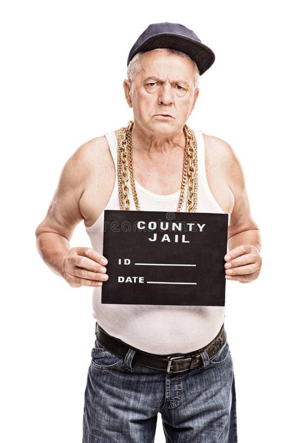 Älterer Gangster, der für ein Verbrecherfoto aufwirft stockbilder