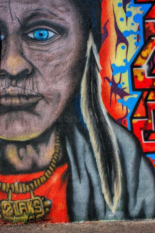 Älterer, gealterter Indianer mit Halskette und buntes Graffitiwandgemälde der Feder auf der Wand stockbilder