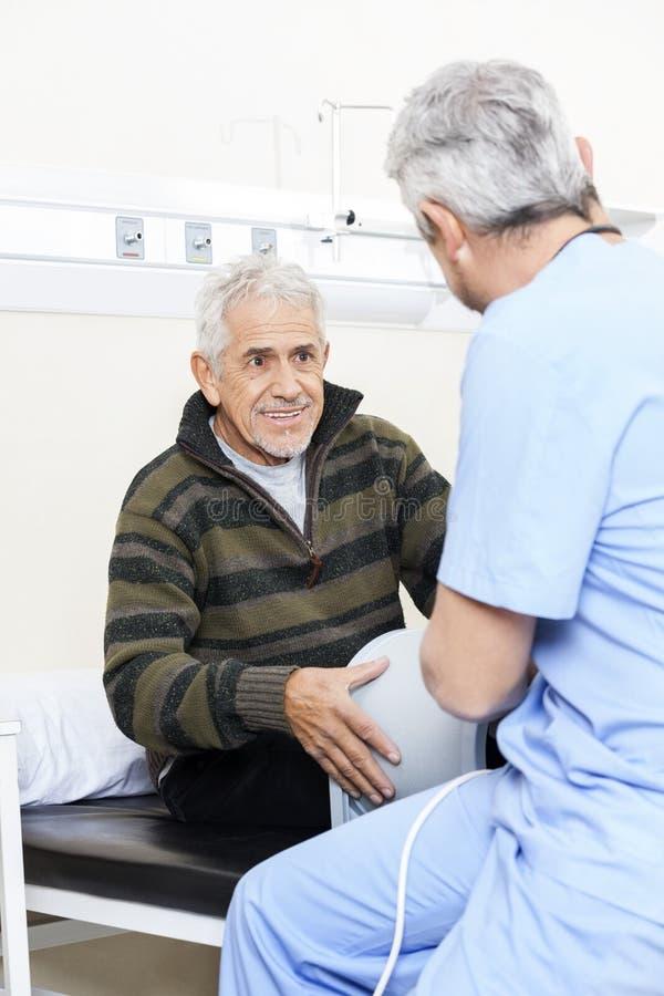 Älterer geduldiger schauender Physiotherapeut On Bed lizenzfreies stockbild