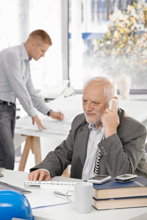 Älterer Geschäftsmann, der am Überlandleitungtelefon spricht lizenzfreies stockfoto