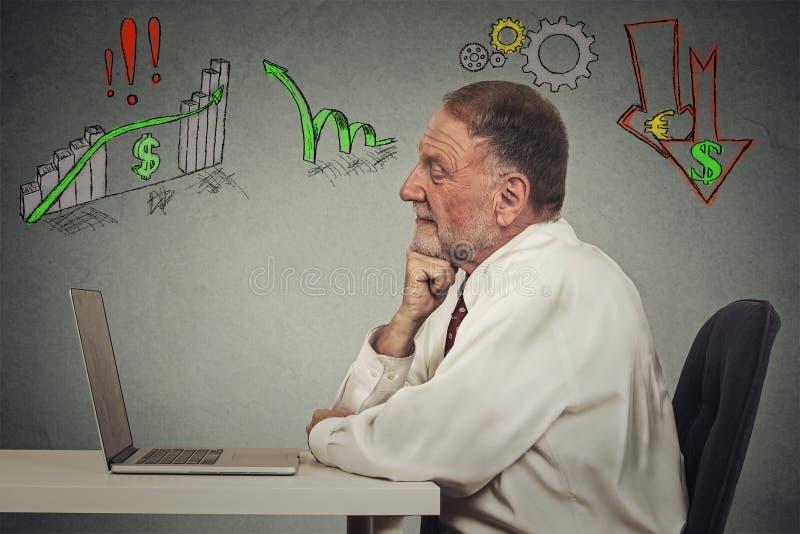 Älterer Geschäftsmann, der an Computer arbeitet stockfoto