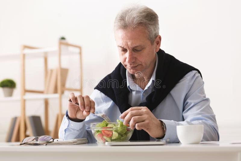 Älterer Geschäftsmann, der Frischgemüsesalat, Bruch habend isst stockfotografie