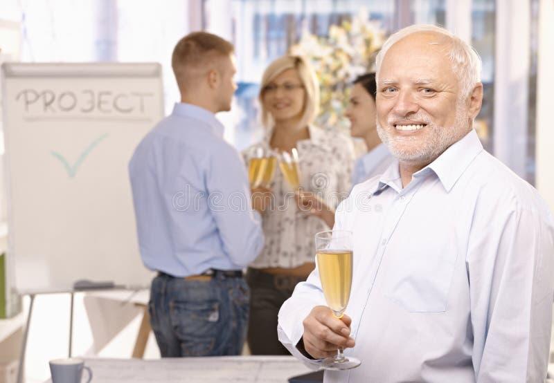 Älterer Geschäftsmann, der im Büro feiert lizenzfreie stockfotografie