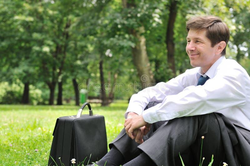 Älterer Geschäftsmann, der im Gras stationiert lizenzfreies stockfoto