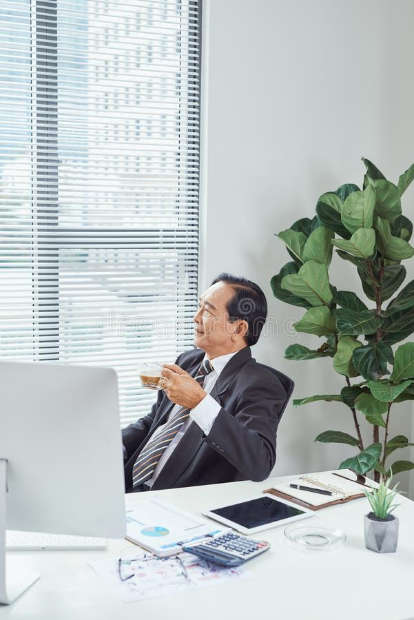 Älterer Geschäftsmann, der an seinem Schreibtisch im Büro sich entspannt stockbilder