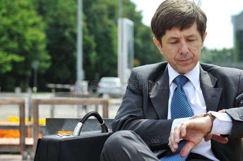 Älterer Geschäftsmann, der Uhren betrachtet stockfotos