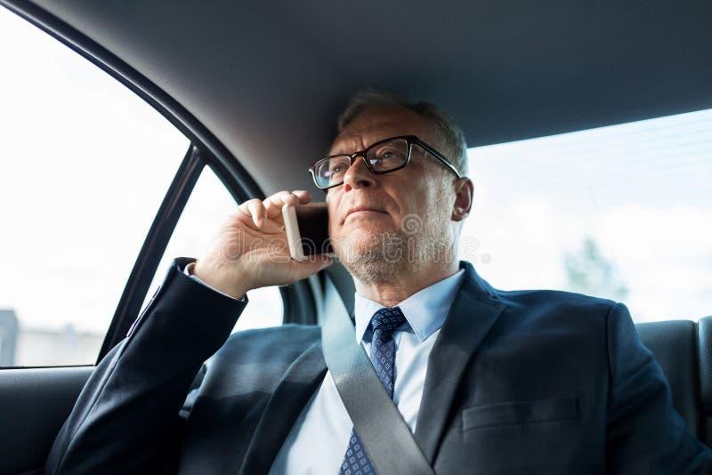 Älterer Geschäftsmann, der um Smartphone im Auto ersucht stockfotos