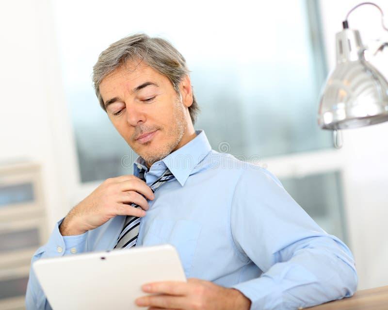 Älterer Geschäftsmann mit Tablette stockfotografie