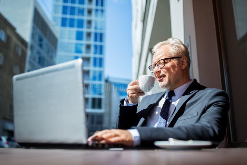 Älterer Geschäftsmann mit trinkendem Kaffee des Laptops lizenzfreie stockbilder