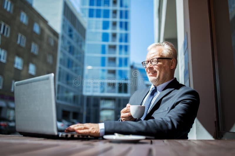 Älterer Geschäftsmann mit trinkendem Kaffee des Laptops lizenzfreies stockbild