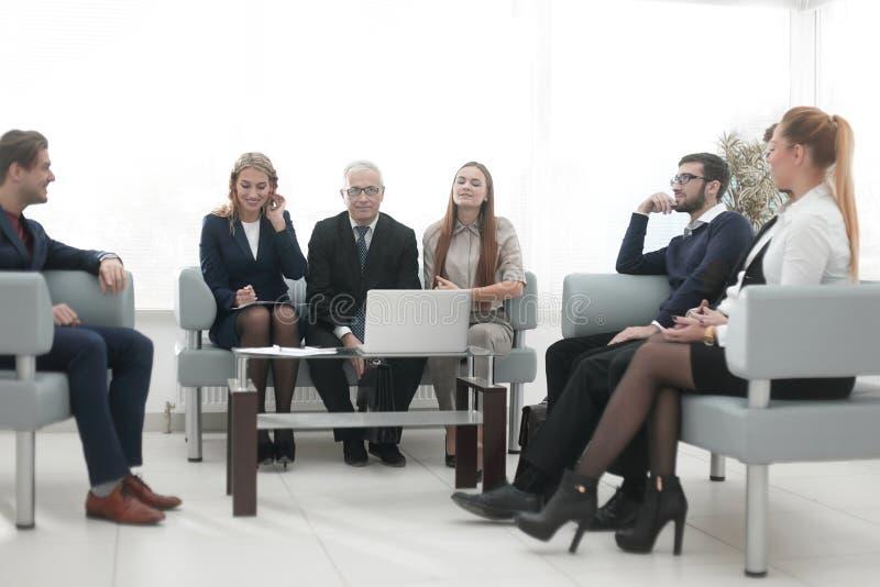 Älterer Geschäftsmann und Geschäft team das Sitzen in der Lobby des modernen Büros stockbild