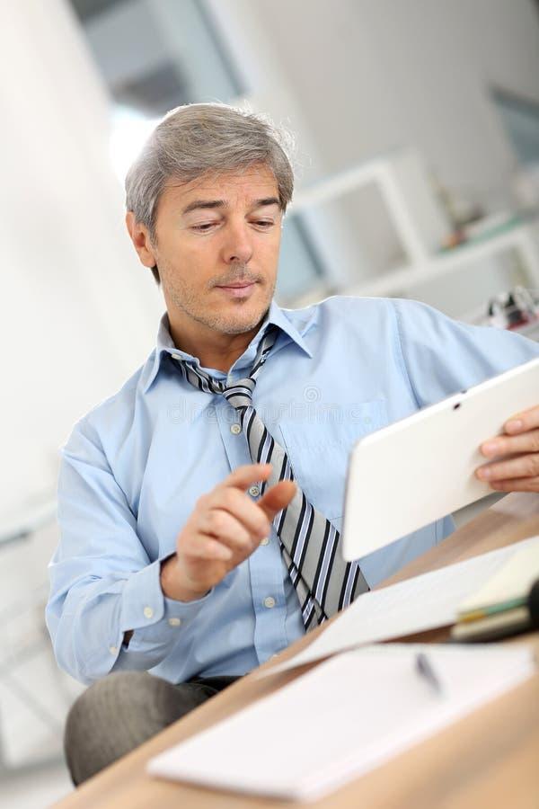 Älterer Geschäftsmann unter Verwendung der Tablette stockbilder