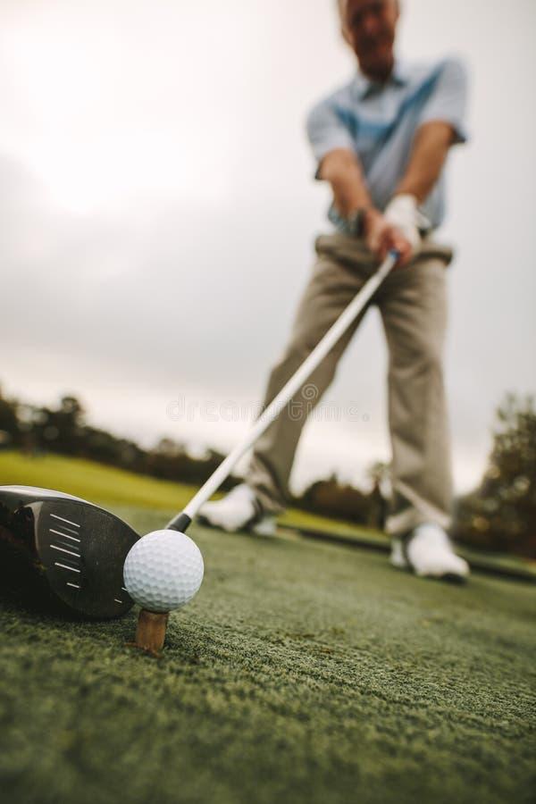 Älterer Golfspieler, der einen Schuss am Golfplatz nimmt lizenzfreie stockfotos