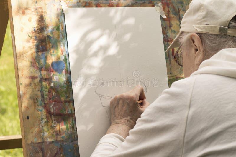 Älterer grau-haariger Mann zeichnet mit der linken Hand am Kunststudio stockbilder