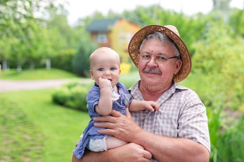 Älterer grauer Mann im Strohhut, der an Hand Enkel hält und Spaß im grünen Sommergarten hat Baby mit grandgather genießend zu stockfoto