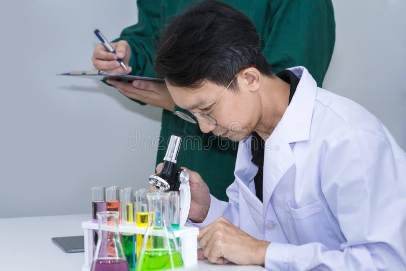 Älterer hübscher Forscher mit Mikroskopen und Farbreagenzglas lizenzfreie stockfotografie