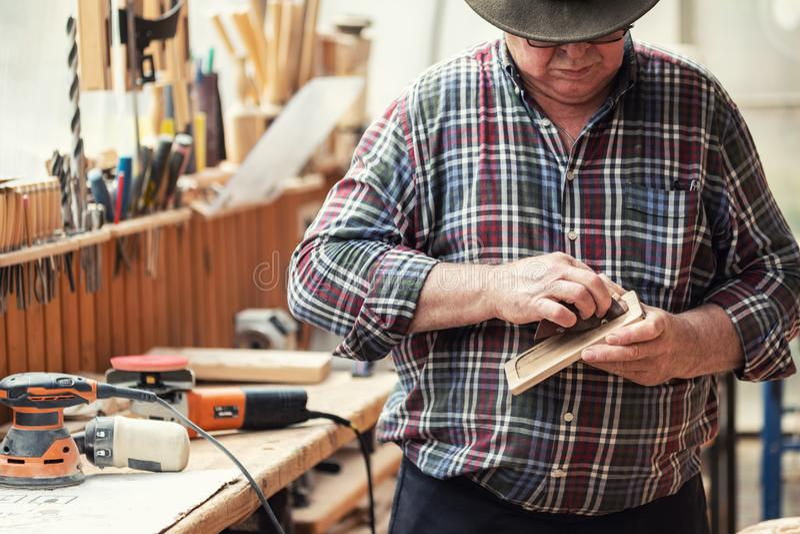 Älterer Handwerker, der hölzernes Teil mit Sandpapierschleifermaschine an der Zimmereiwerkstatt reibt Reife Vorlagenpolierdetails lizenzfreie stockbilder