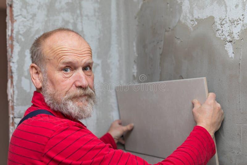 Älterer Handwerker, der mit Fliesen arbeitet stockfotos