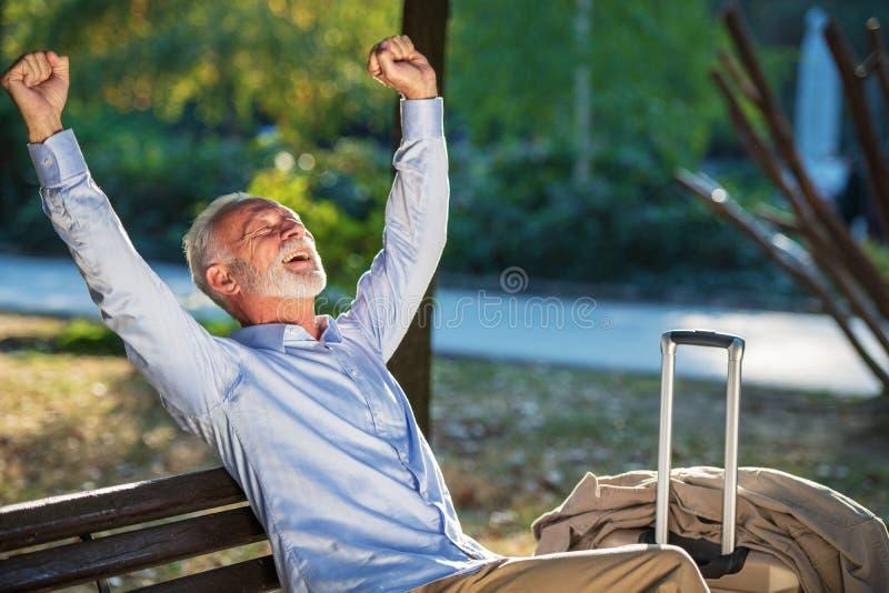 Älterer Herr, der auf einer Holzbank sitzt und in einem Park sich entspannt stockbilder